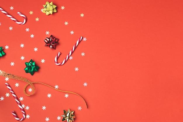 Composição de natal plana leigos, pão de mel, cortador de biscoitos, pirulito, laranja seca, ornamentos e pinha no vermelho