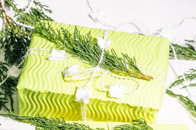 Composição de natal presente com ramos de árvore de abeto decoração branca em caixa de presente amarela