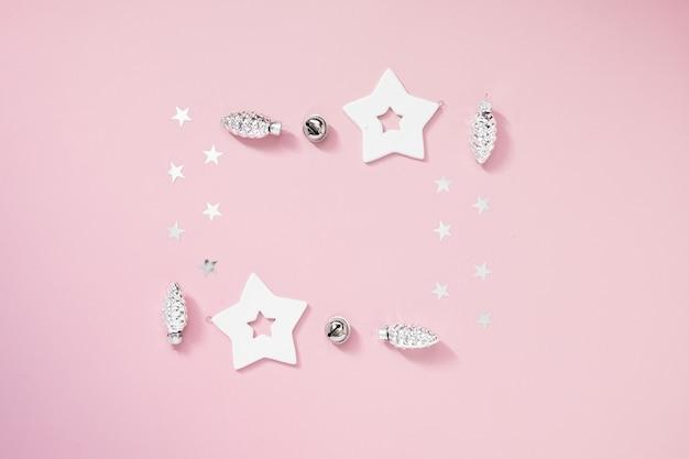 Composição de natal. presentes de natal, enfeites pretos e dourados sobre fundo rosa pastel.
