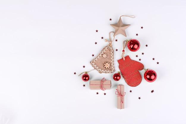 Composição de natal. presentes, galhos de árvore do abeto, decorações vermelhas sobre fundo branco. natal, inverno, conceito de ano novo