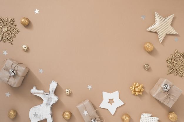 Composição de natal. quadro com presentes, artesanato e decorações douradas sobre fundo bege pastel.