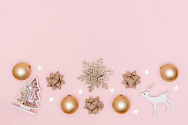 Composição de natal. quadro de bolas douradas, estrelas brancas, floco de neve, árvore de natal, arcos de presente, veado em fundo de papel rosa pastel. vista superior, plana leigos, copie o espaço.