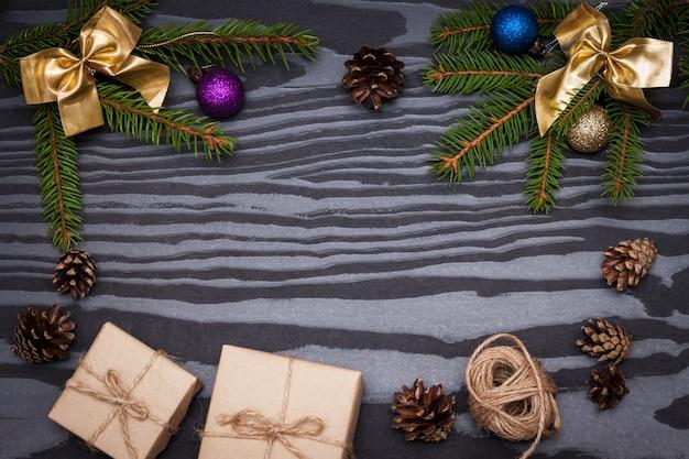 Composição de natal. ramos de abeto, presentes, cones de abeto em fundo preto