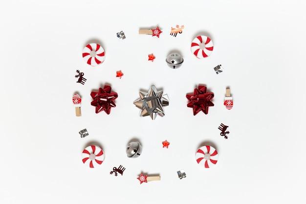 Composição de natal. rodada feita de prendedores de roupa, estrelas, arcos, bulbos de doces, confetes de veado e presentes no fundo branco