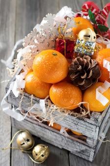 Composição de natal. tangerinas frescas e brinquedos de ano novo em uma caixa no fundo de madeira velho. estilo rústico