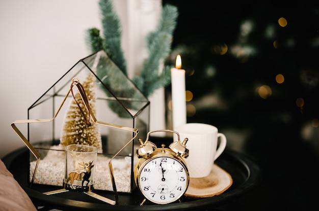 Composição de natal. vela, xícara de café, relógio de ouro vintage, castiçal de ouro de metal em forma de estrela na mesa. interior e decoração em casa. fechar-se. véspera de férias de natal.