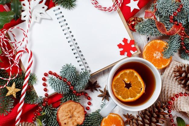 Composição de natal vermelha e dourada com caderno e caneca de chá
