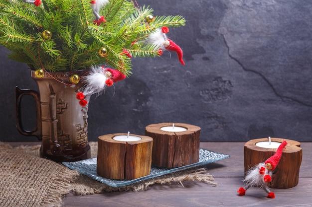 Composição de natal vintage ou ano novo com árvore de natal, velas de madeira e gnomos. estilo rústico.