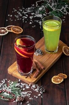 Composição de natureza morta com dois copos de bebida refrescante de inverno vermelha e verde ou vinho quente com fatias de laranja em um fundo escuro de madeira com neve