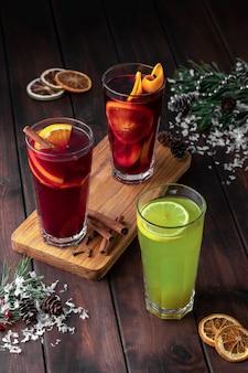 Composição de natureza morta com três copos de bebida refrescante de inverno vermelha e verde ou vinho quente com fatias de laranja em um fundo escuro de madeira com neve