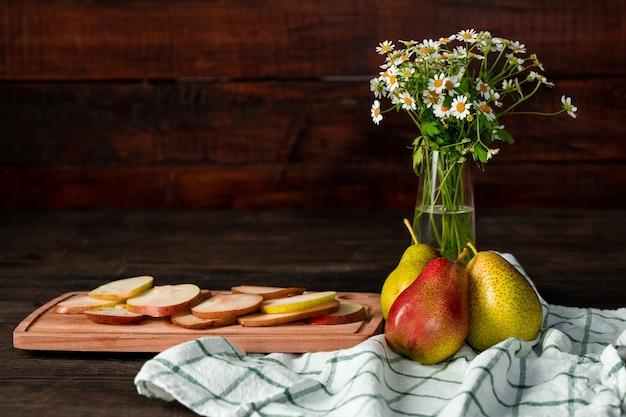 Composição de natureza morta com vaso de flores silvestres, toalha de linho de cozinha, peras maduras e tábua de cortar com fatias de frutas frescas