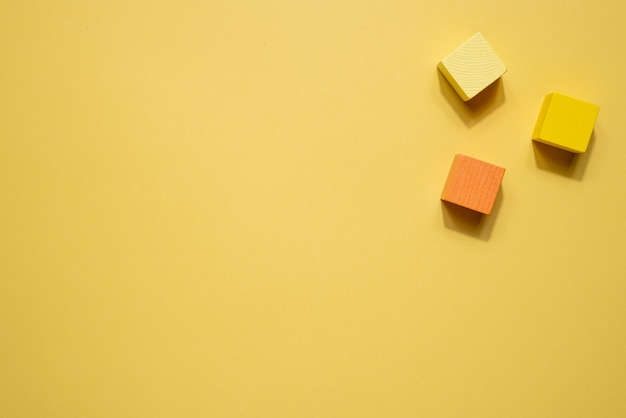 Composição de natureza morta de figuras geométricas amarelas. objetos de cubo de jogo de madeira em fundo amarelo. figuras de sólidos platônicos, conceito de simplicidade topo
