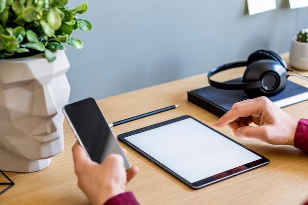 Composição de negócios modernos no escritório em casa com freelancer, simulação de tela do tablet, planta, notas, celular e material de escritório no conceito elegante de decoração para casa.