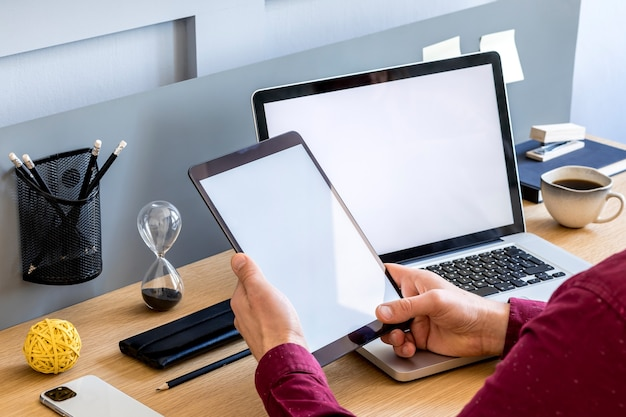 Composição de negócios modernos no escritório em casa com freelancer, simulação de tela do tablet, planta, notas, telefone celular e material de escritório no conceito elegante de decoração para casa.