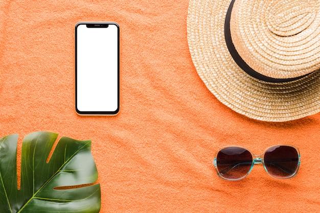 Composição de óculos de sol de chapéu de celular e folha de planta