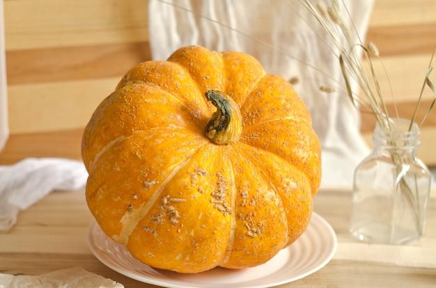Composição de outono. abóbora em chapa branca na mesa de madeira
