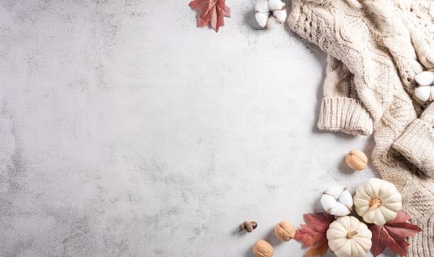 Composição de outono abóbora flores de algodão, folhas de outono e suéter em fundo de pedra