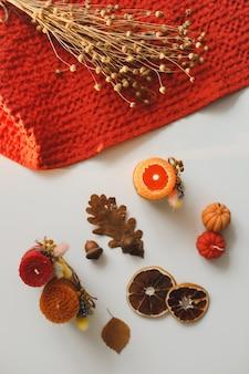 Composição de outono aconchegante com abóbora, velas de cera, folhas secas por fundo de luzes de bokeh
