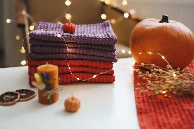 Composição de outono aconchegante com folhas de abóbora e tecido