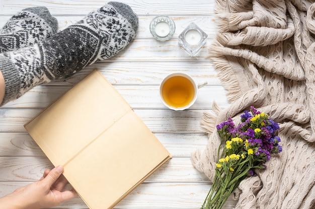 Composição de outono aconchegante com mulher em meias de lã quentes com um livro velho aberto e uma xícara de chá de ervas.