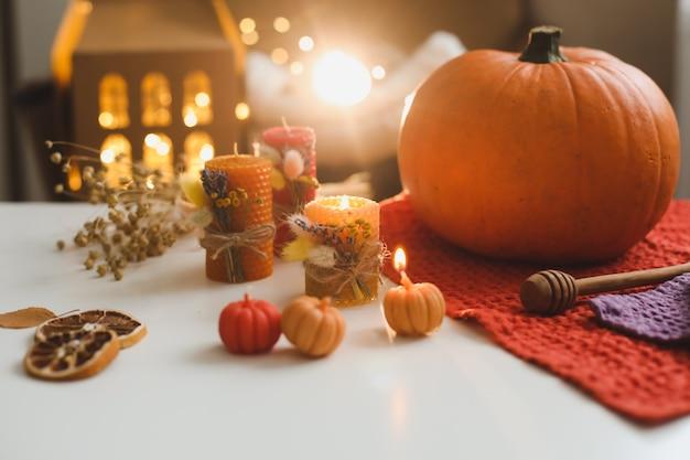 Composição de outono aconchegante com velas de cera de abóbora e folhas
