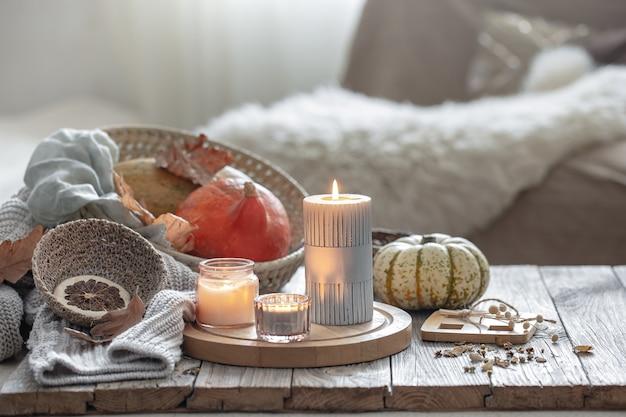 Composição de outono aconchegante com velas e abóboras no interior de uma casa.