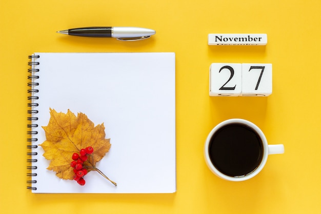Composição de outono. calendário de madeira 27 de novembro xícara de café