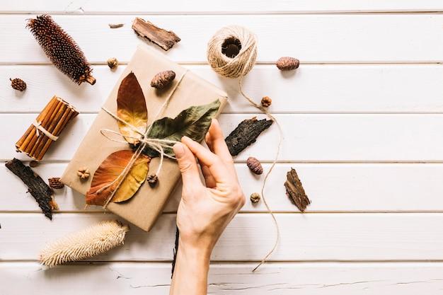Composição de outono com a mão segurando a corda de presente