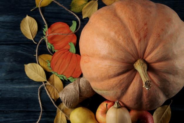 Composição de outono com abóbora e frutas de outono com maçãs e peras em uma mesa azul escura e em um fundo preto