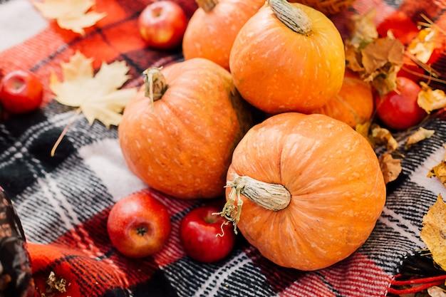 Composição de outono com abóboras, folhas de bordo e maçãs vermelhas