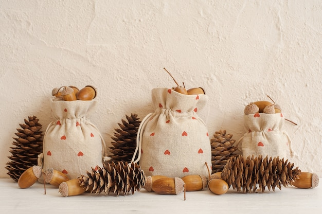 Composição de outono com bolotas em sacos de linho e pinhas. outono, conceito de outono.