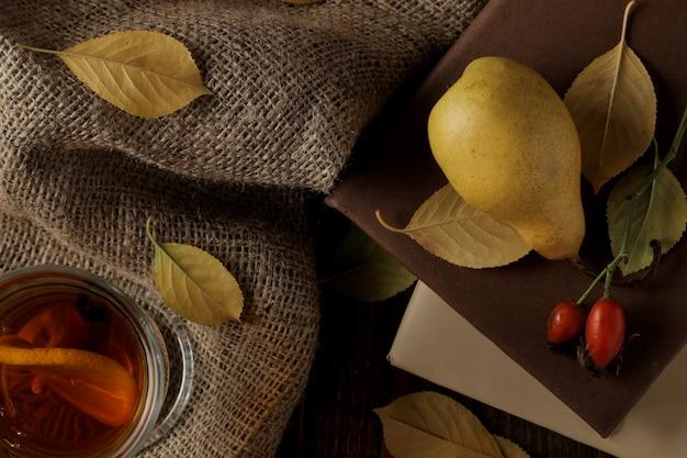 Composição de outono com chá quente de peras, livros e rosa mosqueta. vista do topo