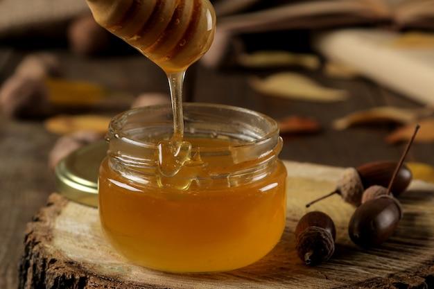 Composição de outono com close-up de mel e bolotas em um suporte de madeira sobre uma mesa de madeira marrom.