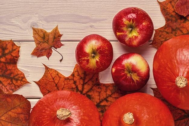 Composição de outono com folhas coloridas, maçãs e abóboras na superfície de madeira.