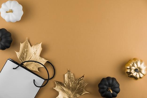 Composição de outono com folhas de bordo douradas, abóboras decorativas e sacola de compras