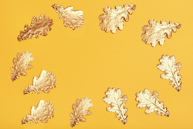 Composição de outono com folhas douradas na superfície de papel amarelo