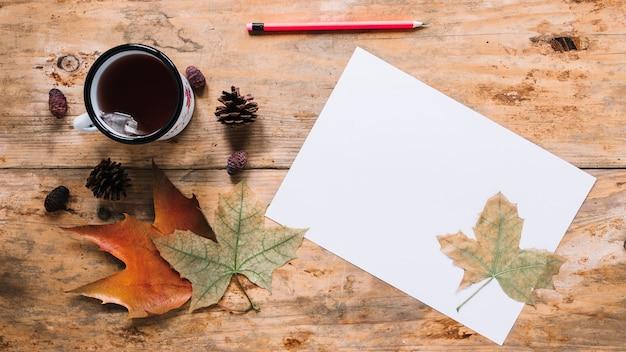 Composição de outono com folhas e chá em fundo de madeira
