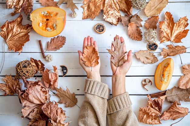 Composição de outono com folhas secas, mãos femininas e abóbora em plano de fundo de madeira branco leigo.