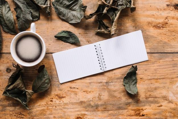 Composição de outono com folhas secas, xícara de café e notebook