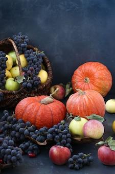 Composição de outono com maçãs, uvas, abóbora e dogwood