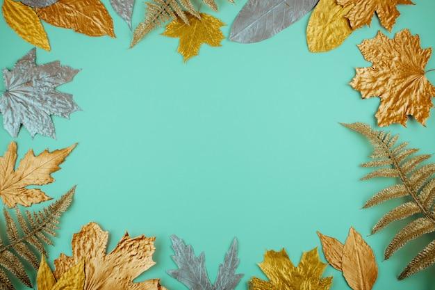 Composição de outono com moldura de folhas douradas sobre fundo azul hortelã
