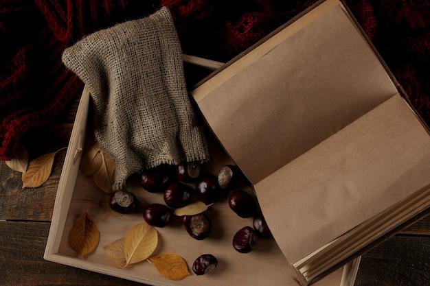 Composição de outono com uma bandeja quente e castanhas e um livro sobre um fundo de madeira marrom
