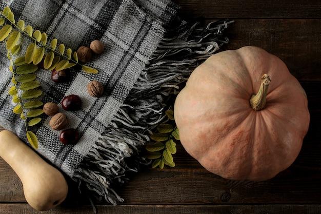 Composição de outono com uma manta de abóbora e castanheiros em uma mesa de madeira marrom. vista do topo