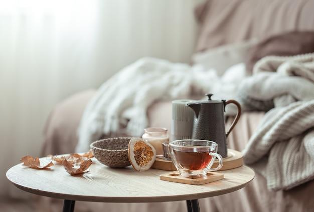Composição de outono com uma xícara de chá, um bule e detalhes de decoração de outono em um fundo desfocado.