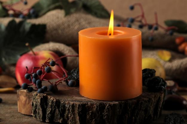 Composição de outono com velas e frutas de outono e bagas e castanhas em uma mesa de madeira marrom