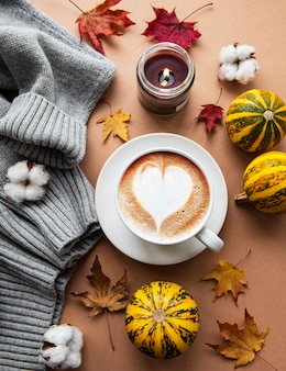 Composição de outono com xícara de café, cobertor quente, abóboras listradas decorativas, velas e folhas de outono