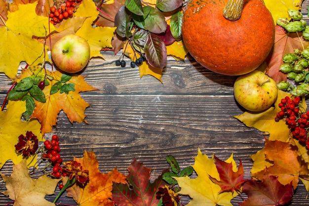 Composição de outono de maçãs, folhas, abóboras em um fundo de madeira marrom escuro.