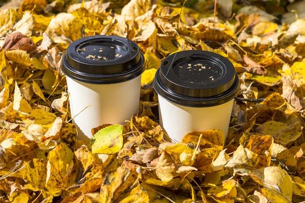 Composição de outono. duas xícaras de café em um toco no parque. café para ir entre as folhas de outono. conceito de piquenique de outono. c