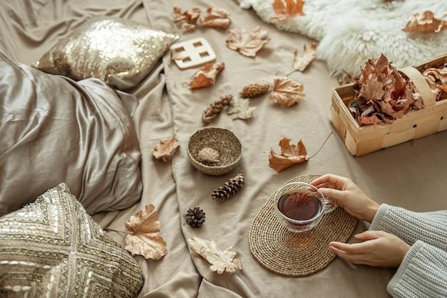 Composição de outono em casa com mãos femininas e uma xícara de chá na cama, entre pinhas e folhas de outono.