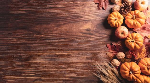Composição de outono flores de algodão de abóbora e folhas de outono em fundo escuro de madeira